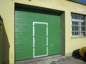Brama przemysłowa segmentowa Wiśniowski Makropro z drzwiami przejściowymi, struktura panela: woodgrain, kolor: RAL:6005